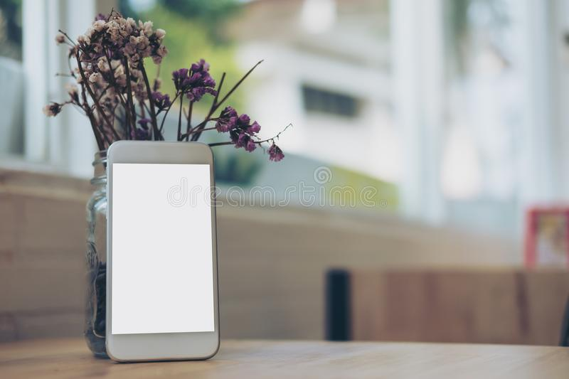 White mobile phone with blank white screen with flower vase on wooden table in modern cafe. Mockup image of white mobile phone with blank white screen with royalty free stock images