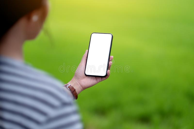 A woman holding black mobile phone with blank desktop screen with blur green nature background stock photos