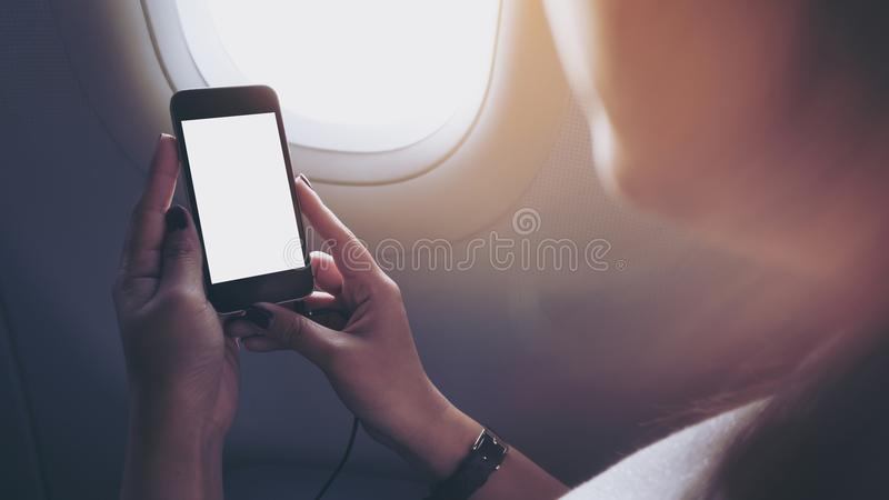 Mockup image of a woman holding and looking at black smart phone with black white screen next to an airplane window royalty free stock photo