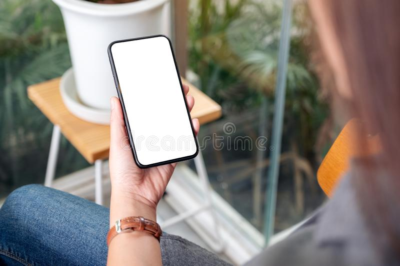 A woman holding and using black mobile phone with blank desktop screen in cafe royalty free stock images