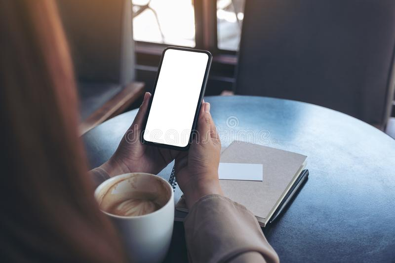Woman holding and using a black mobile phone with blank screen for watching with notebook and coffee cup on wooden table royalty free stock photo