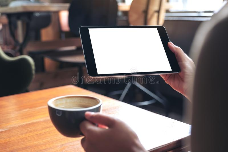 Woman`s hands holding black tablet pc with blank white screen while drinking coffee on wooden table in cafe royalty free stock photos