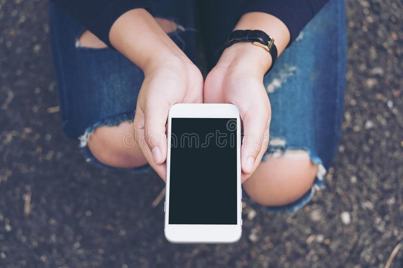 Mockup image of a woman sitting on the street and holding white mobile phone. With blank black screen royalty free stock images