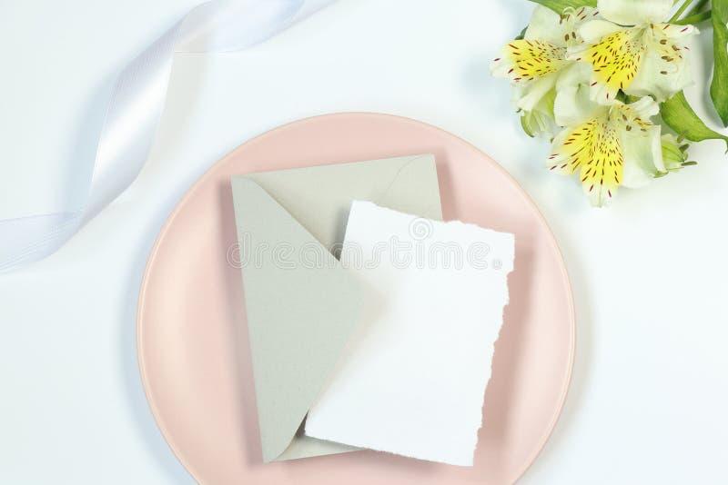 Mockup kartka z pozdrowieniami na menchia talerzu, bia?y t?o z kwiatami i faborek, fotografia royalty free