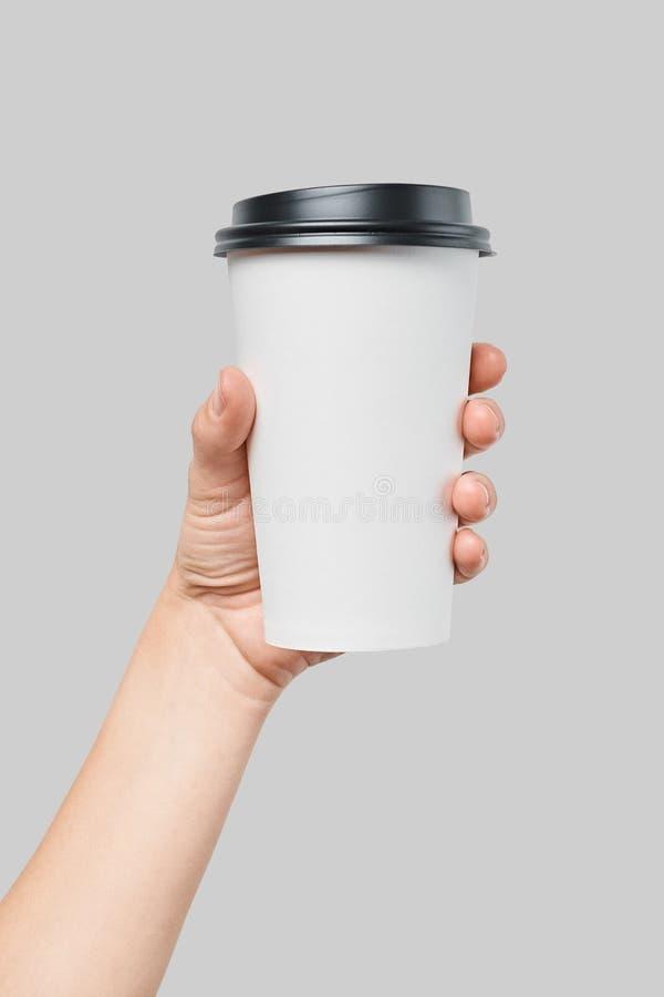 Mockup kobiety ` s ręka trzyma białego papieru ampuły rozmiaru filiżankę z czerni pokrywą zdjęcie stock