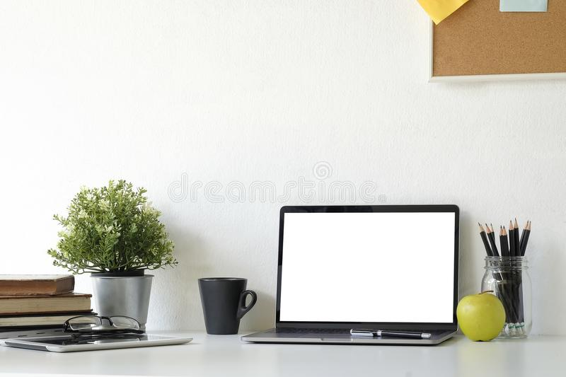 Mockup laptop computer on Stylish table Board and post it, book, pencil, glasses  and coffee mug with tablet on table with wall. stock image