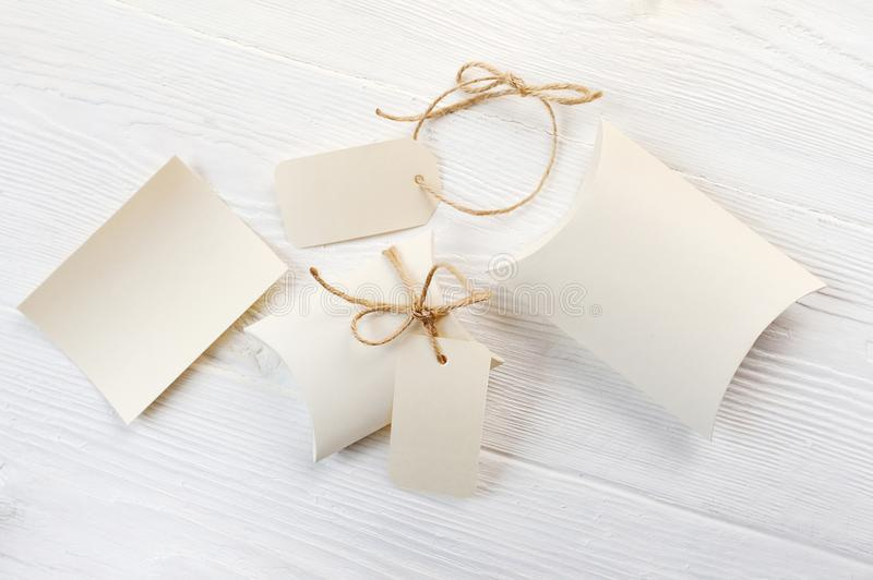 Mockup letter, boxes of bonbonniere and tag with place for your text on a white wooden background royalty free stock images