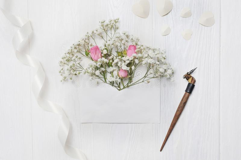 Mockup Letter with flowers and calligraphic pen greeting card for St. Valentine`s Day in rustic style with place for stock photos
