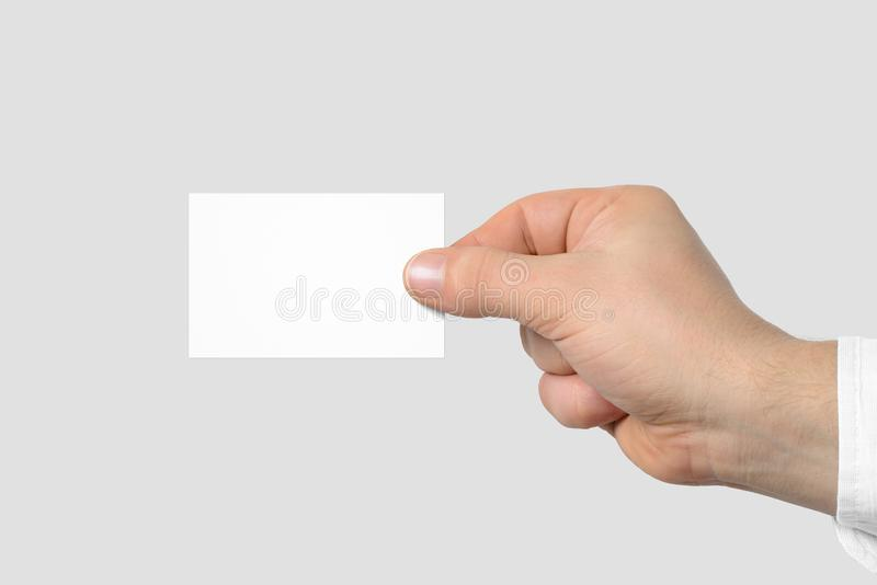 Mockup of male hand holding a Business Card isolated on light grey background. royalty free stock images