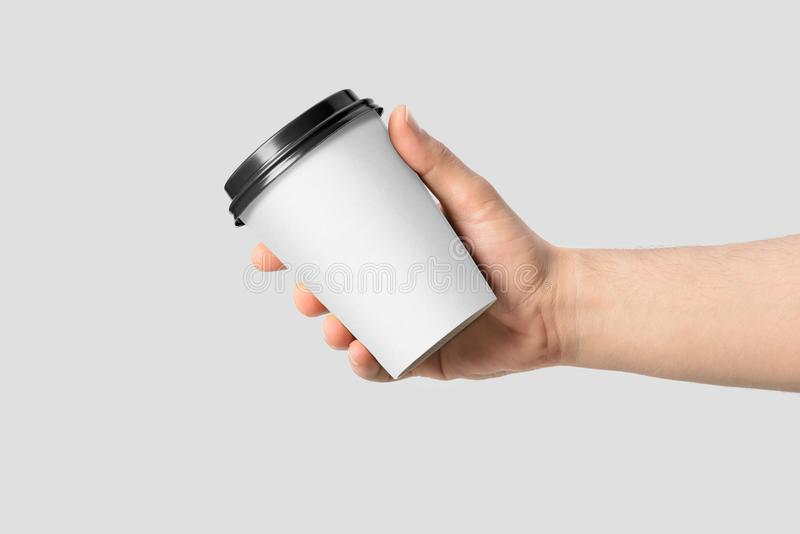 Mockup of male hand holding a Coffee paper cup. stock photo