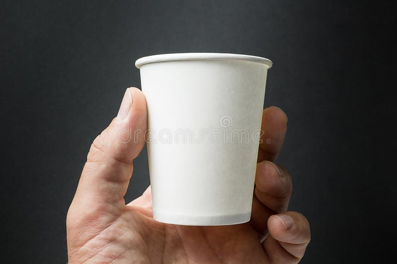 Mockup of male hand holding a Coffee, Tea or Juice paper cup isolated on black background royalty free stock photo