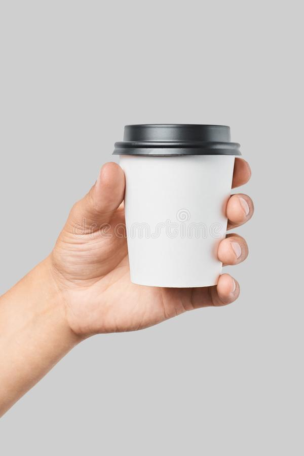 Mockup of men`s hand holding white paper small size cup with black cover royalty free stock images
