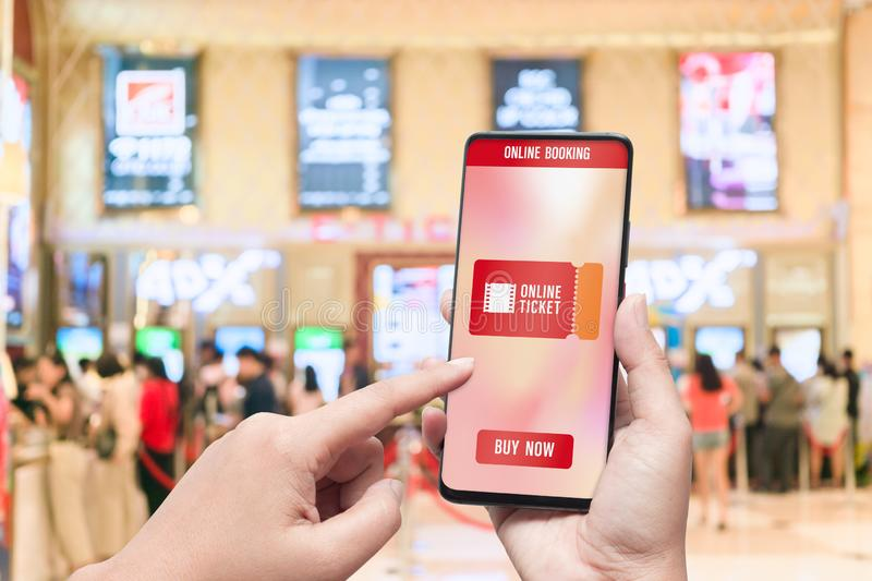 Mockup mobile phone hand using smartphone to buy cinema tickets with blurred image of ticket sales counter at movie theater with. Graphic icon, online booking stock photos