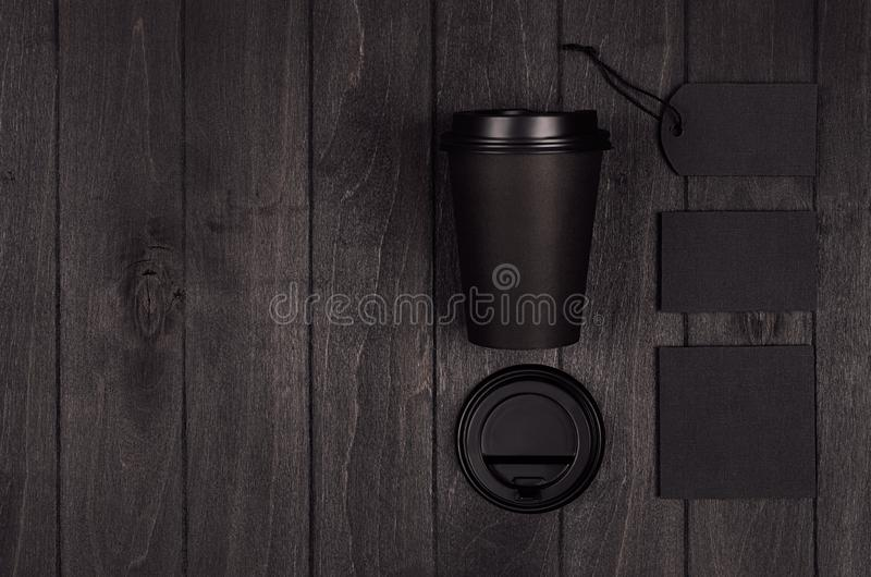 Mockup packing for coffee products and shop - black paper cup, blank label, card, stationery, sugar on dark black wood table. royalty free stock photography