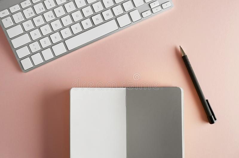 Mockup of paper note book, computer keyboard on empty color desk. Business empty mock-up background for message writing. Top view royalty free stock image