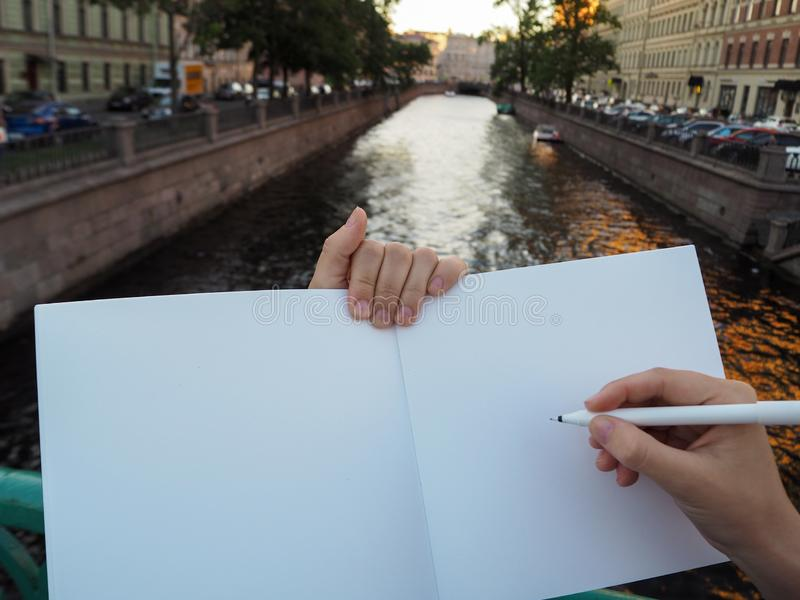 Mockup of person hand holding blank white notebook preparing to write down his or hers ideas. stock photography