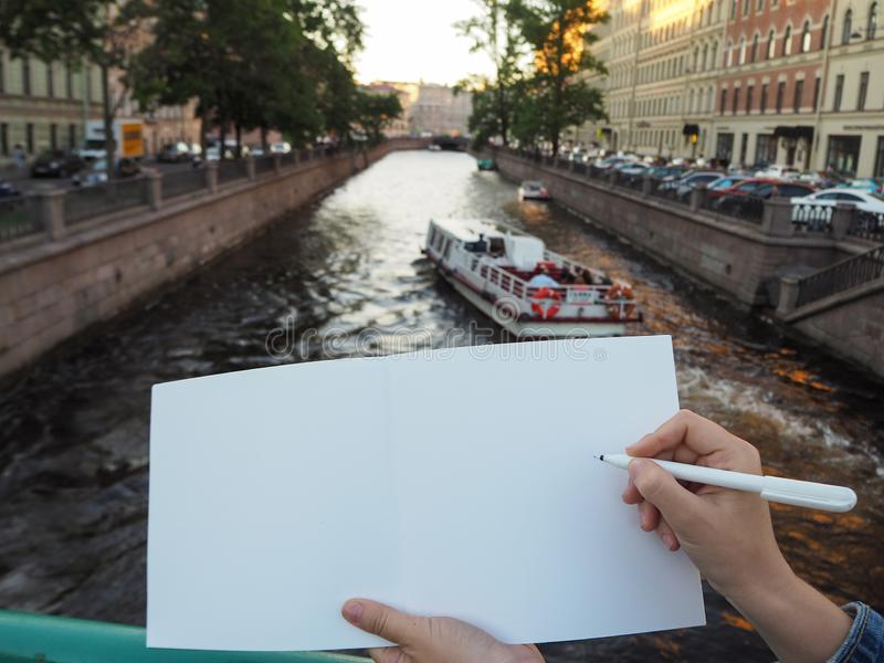 Mockup of person`s hand holding blank white notebook preparing to write down his or hers ideas. royalty free stock photo