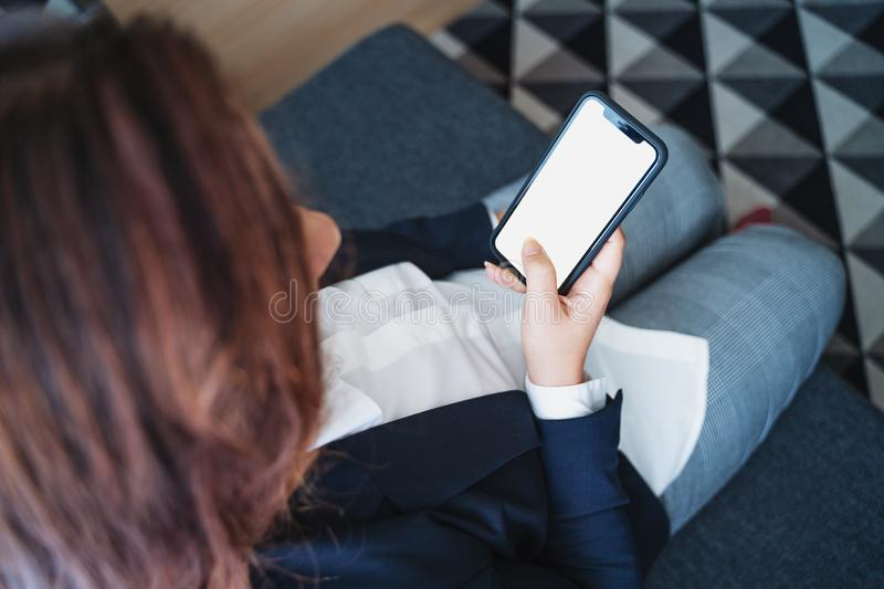 Mockup photo of female hand holds smartphone or mobile phone with white screen as blank space, selective focus royalty free stock photos
