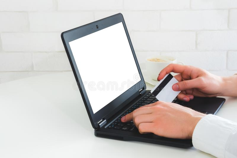 Mockup photo with laptop and man hands holding credit card. Entering verification code. Online payment concept stock images