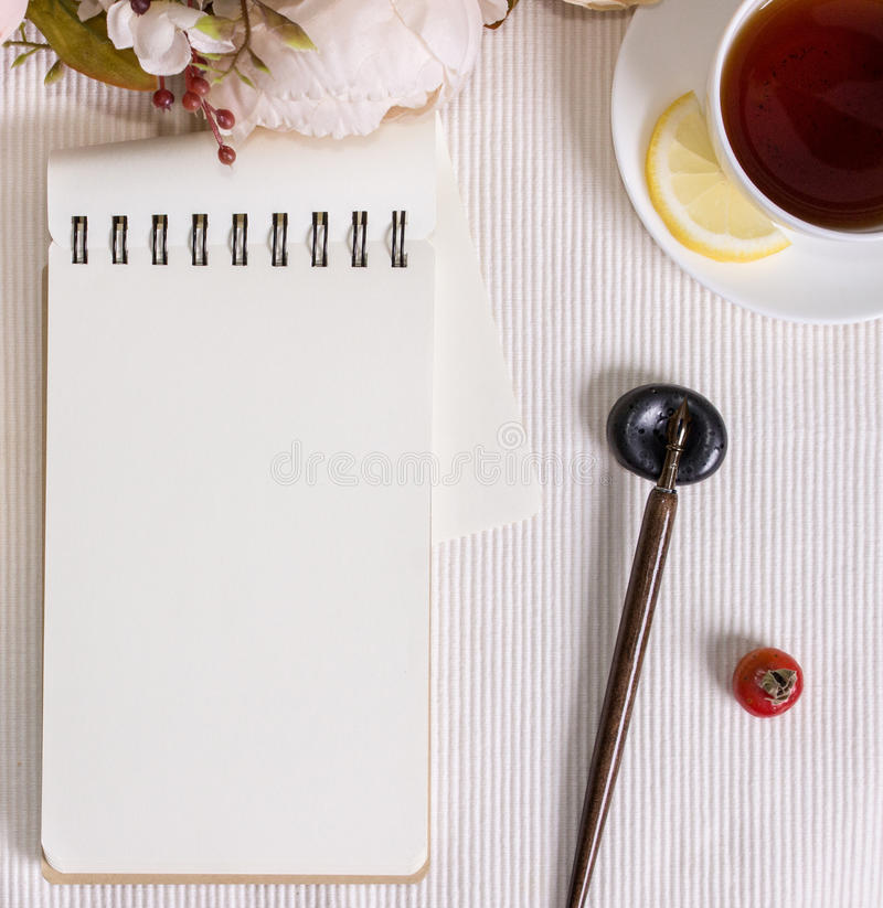 Mockup photography with flowers, notebook, pen and tea royalty free stock images