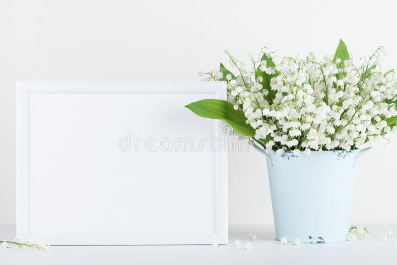 Mockup of picture frame decorated flowers in vase on white background with clean space for text. royalty free stock images