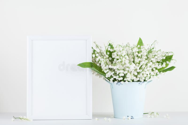 Mockup of picture frame decorated flowers in vase on white background with clean space. stock photo