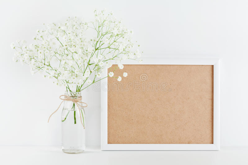 Mockup of picture frame decorated flowers in vase on white working desk with clean space for text and design your blogging. royalty free stock image