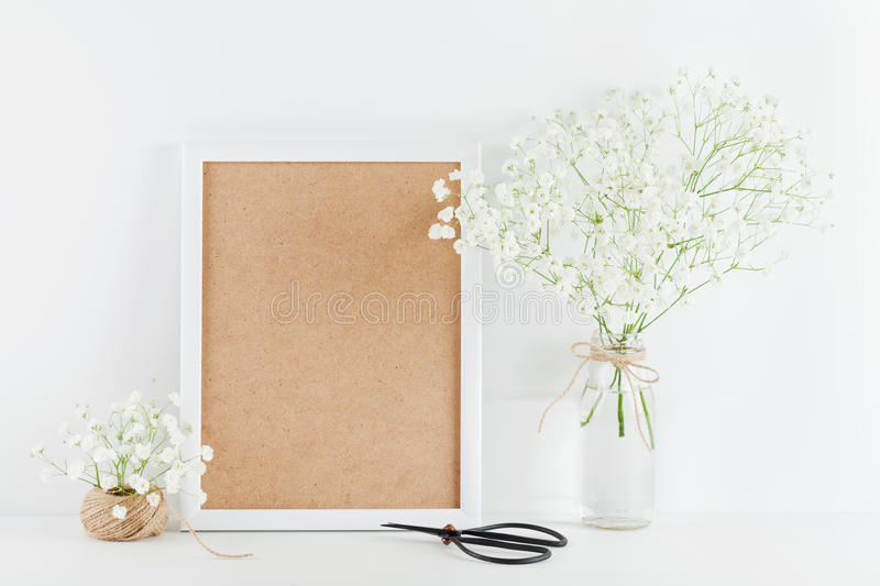 Mockup of picture frame decorated gypsophila flowers in vase on white working desk with clean space for text and design your blogg royalty free stock photos