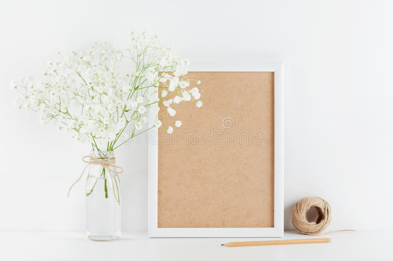 Mockup of picture frame decorated gypsophila flowers in vase on white working table with clean space for text and design your blog stock photography