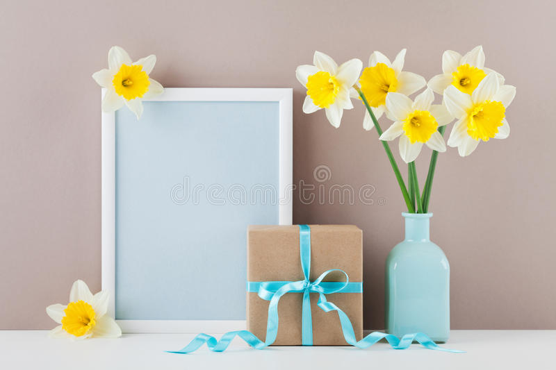 Mockup of picture frame decorated narcissus or daffodil flowers in vase and gift box for greeting on mother day. royalty free stock images