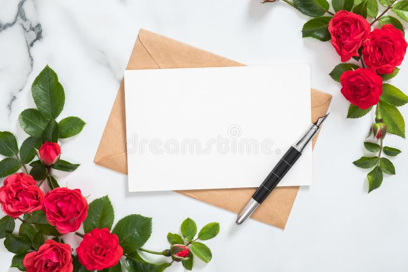 Mockup postcard with craft paper envelope, pen and rose flowers frame on marble stone background. Minimal style composition, flat. Lay. top view. Love letter royalty free stock images