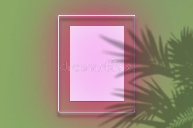 Mockup poster in a neon frame with a pink glow. Scene with tropical overlay palm shadows with free space inside. Mockup poster in a neon frame with a pink glow stock images