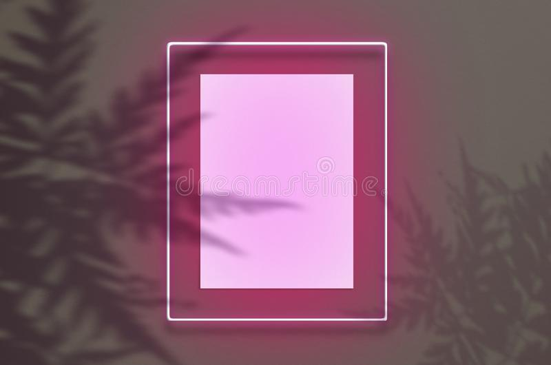 Mockup poster in a neon frame with a pink glow. Scene with tropical overlay palm shadows with free space inside. Mockup poster in a neon frame with a pink glow royalty free stock images