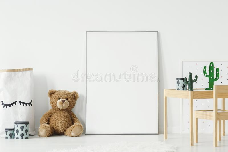 Mockup poster, teddy bear and material basket placed on the floor in white room interior with wooden table and small chair. Paste royalty free stock image