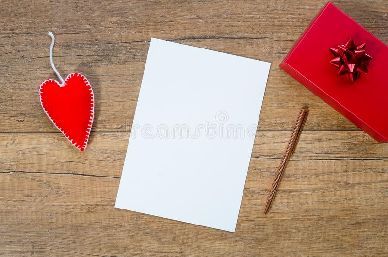 Mockup romantic postcard with felt heart and red giftbox. Flat lay with copy space for text stock image