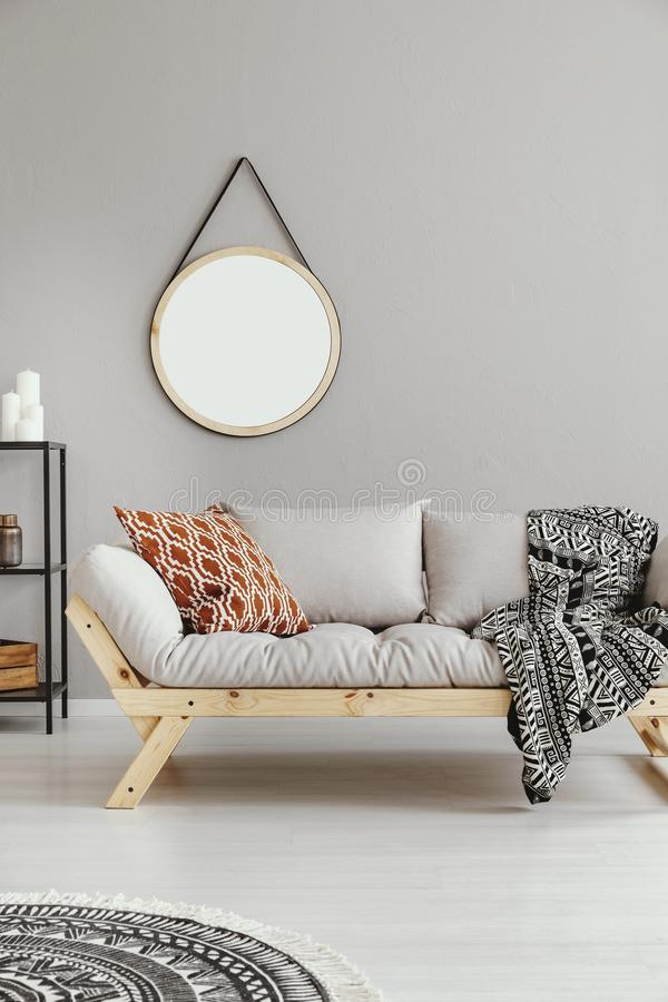 Round mirror above grey settee with patterned blanket. Real photo stock images