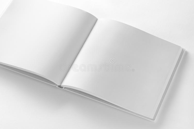 Mockup rozpieczętowana pusta kwadratowa książka przy białym projekta papierem obrazy stock