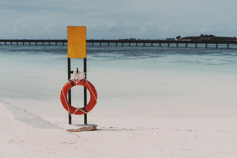 Mockup of safety banner on the beach with the lifebuoy royalty free stock image