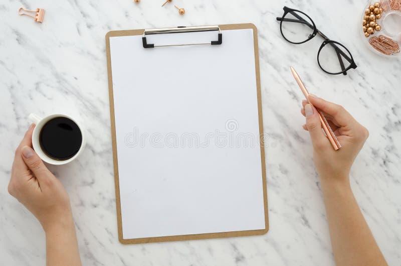 Mockup schowek na marmurowym tle z pustym białej księgi prześcieradłem Odgórnego widoku kobiety ręki trzymają złotego pióro i kaw obraz royalty free