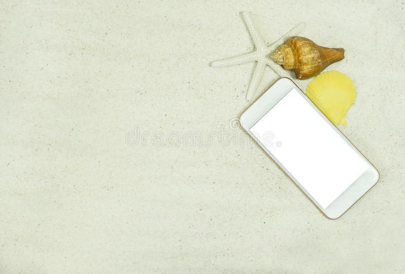 Mockup smartphone on sand beach with seashells. stock photography