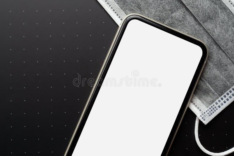 Mockup tom, vit skärmmobiltelefon med ansiktsmasker för Coronavirus eller Covid-19-bakgrundskoncept Ta fram plattan för smartphon fotografering för bildbyråer