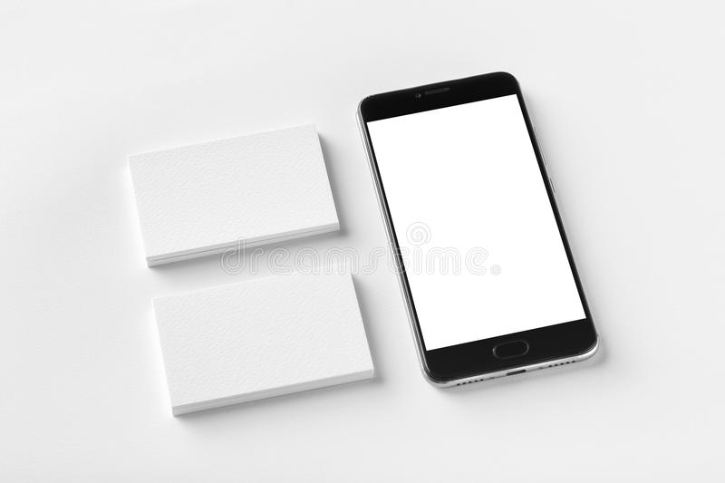 Mockup of two blank horizontal business cards and black cell-phone at white textured paper stock image