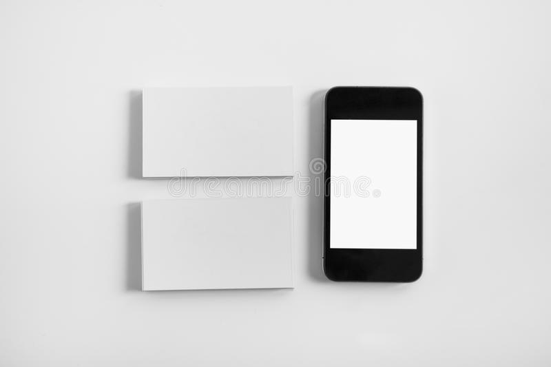 Mockup of two business cards and cell phone with blank screen royalty free stock photo