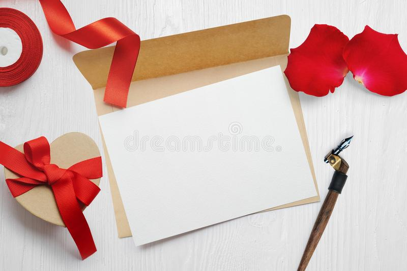 Mockup Valentines Day greeting card letter in envelope with kraft gift box red ribbon, flat lay on a white wooden royalty free stock photography