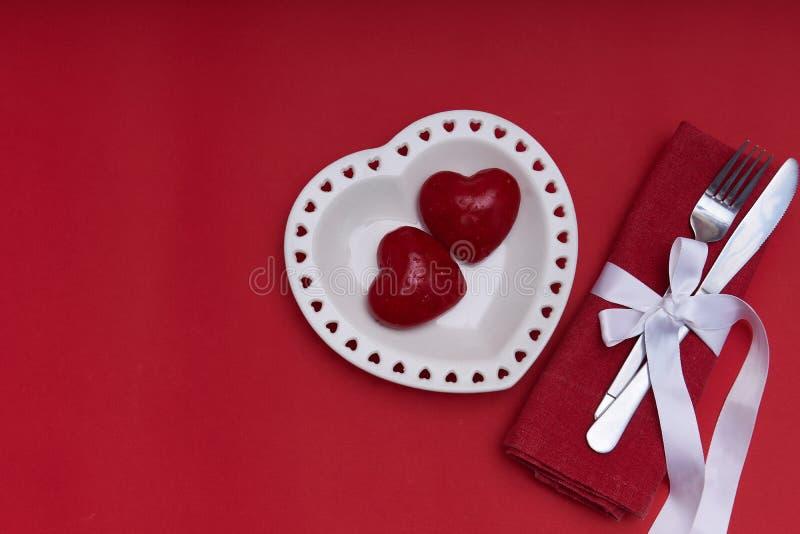 Mockup Valentines Piastra bianca a forma di cuore e posate su sfondo rosso Spazio di copia fotografia stock libera da diritti