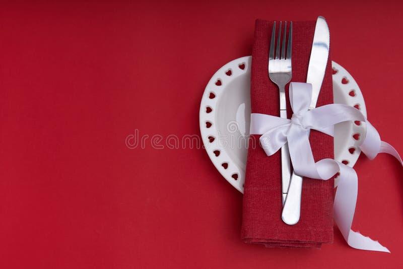 Mockup Valentines Piastra bianca a forma di cuore e posate su sfondo rosso Spazio di copia immagini stock