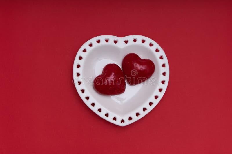 Mockup Valentines Piastra bianca a forma di cuore su sfondo rosso Spazio di copia immagine stock