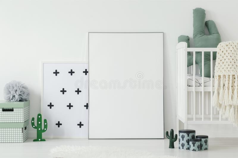 Mockup of white empty poster next to cradle in kid`s room interi. Or with cactus motif. Real photo wit a place for your graphic design stock photo