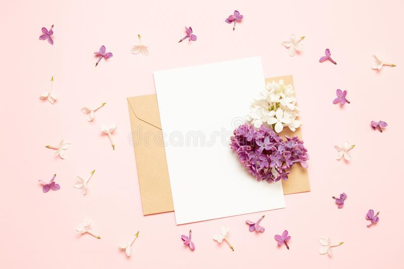 Mockup white greeting card and envelope with branches of lilac on a pink background stock photography