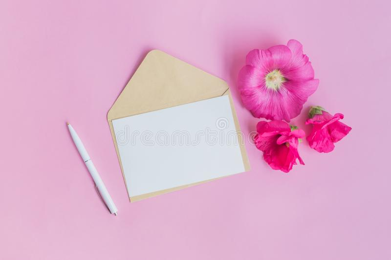 Mockup white greeting card and envelope with pink flowers. On a pink background stock photos